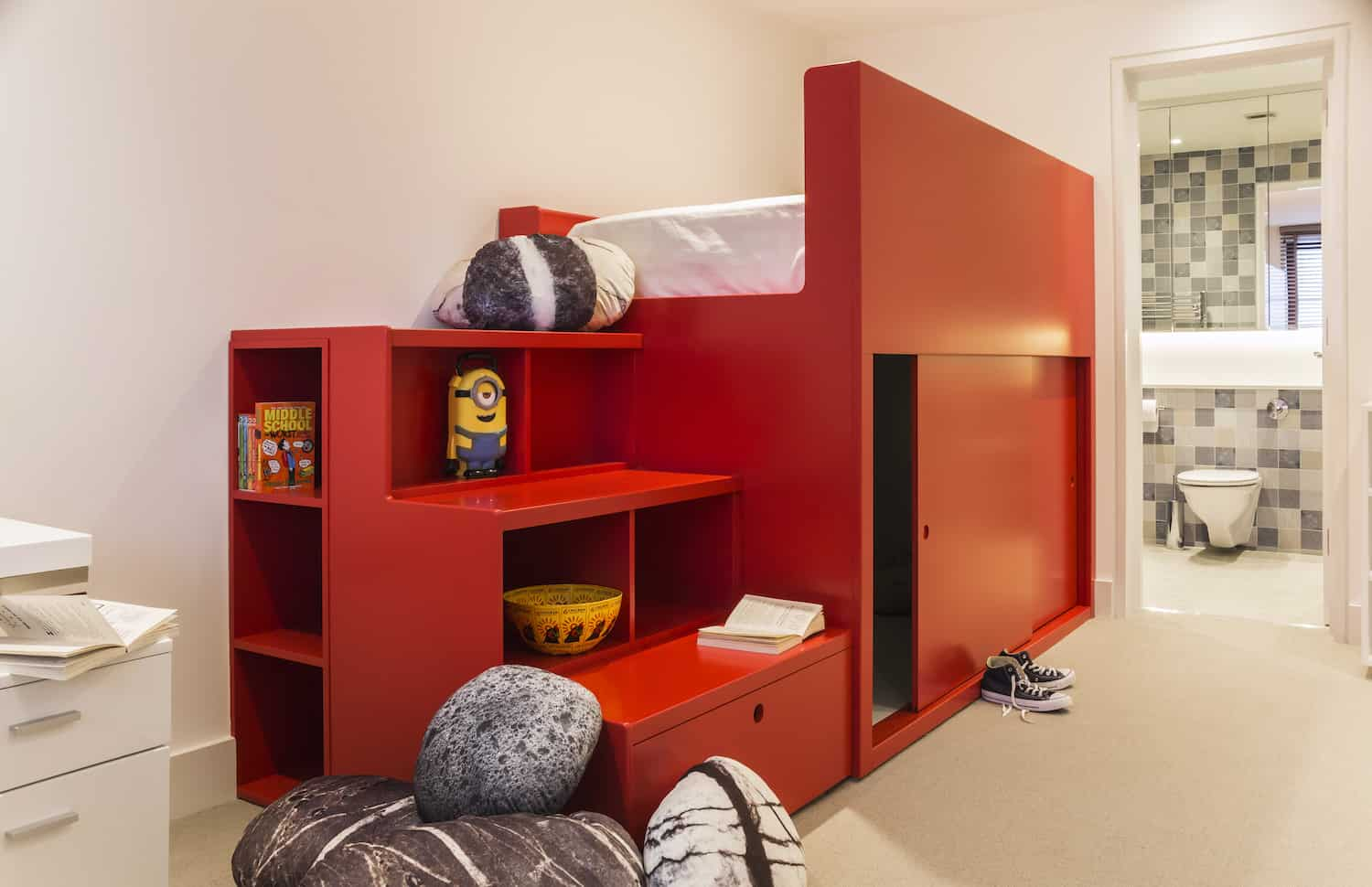 Fabulous kids bedroom with custom built red loft bed with a fort underneath. The wide stairs at the end of the bed unit doubles as shelving. This kids bedroom includes a kids bathroom off the space.