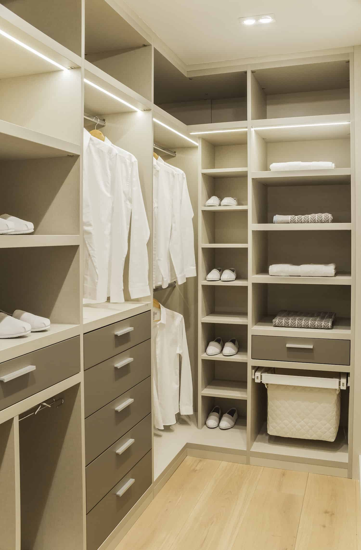 Bright modern closet featuring a hardwood flooring, white and light gray cabinets and beautiful cabinet and recessed ceiling lights.
