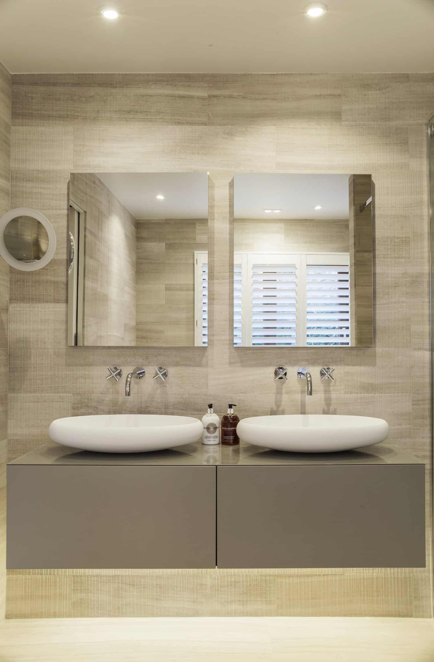 Here's a view of the two white vessel basin sinks with side-by-side mirrors. The basins sit on a modern style floating vanity with lighting underneath.