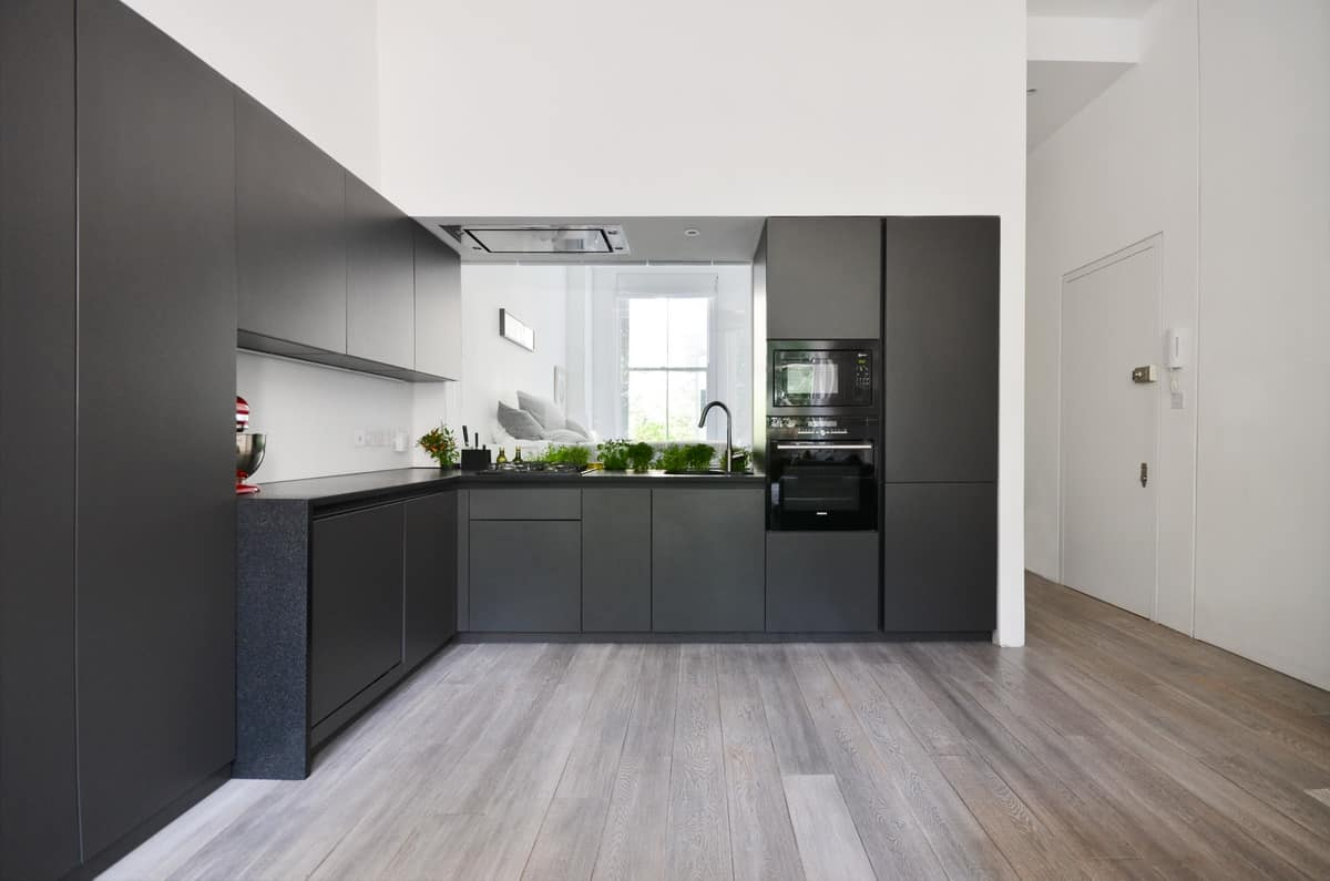 Minimalist black kitchen with modern cabinetry along with a black countertop and black appliances. However, the soaring walls are white which gives the space some brightness along with the medium hardwood flooring.