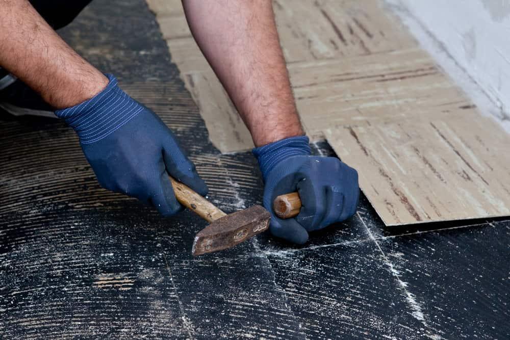 Floor installer removing old linoleum flooring