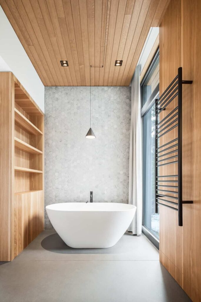 Narrow bathroom features a wood plank ceiling that complements the hardwood wall and built-in storage. It has a freestanding bathtub lighted by a pendant lamp.