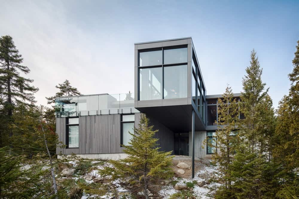 Glazed house built on a steep slope and nestled in pine trees. Its exterior has a neutral color scheme that complements its surrounding.