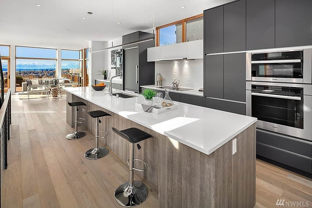 Long single wall modern kitchen with long modern island. Main cabinets are dark gray and the island is natural wood tone.