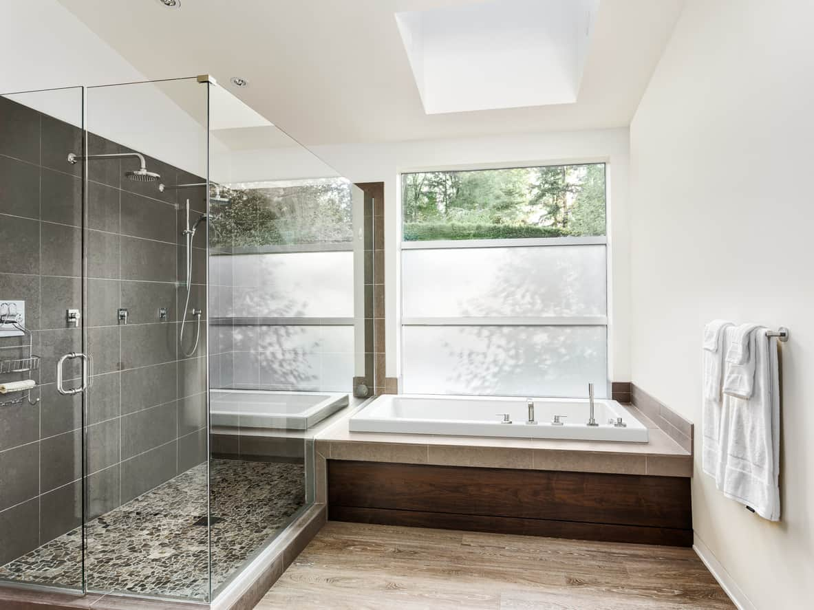 Here's a renovated primary bathroom that is gray, brown and white. I love the skylight and the gray shower color scheme. I'm not so big on the brown, but the layout is really great.