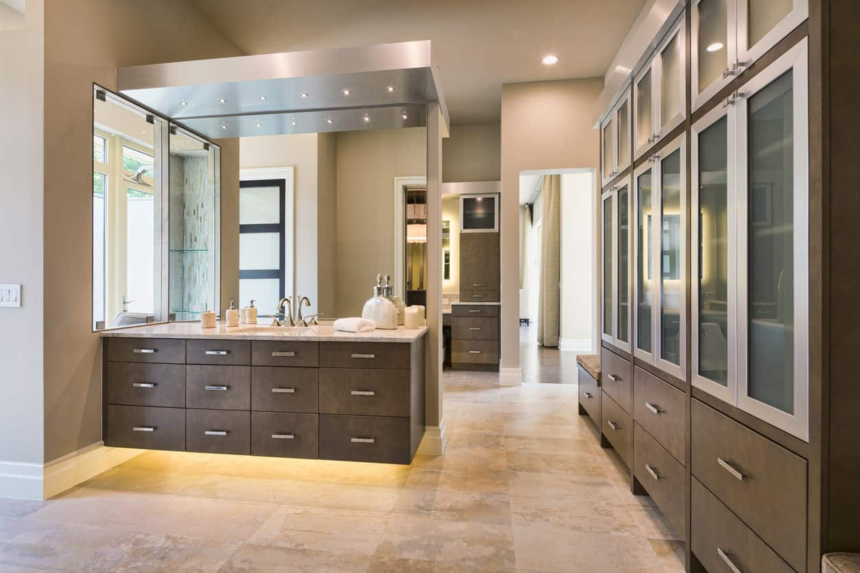 Spacious master bathroom with more storage than most kitchens, which is doubling as a dressing room. I think white flooring would be a better fit here, but those cabinets are amazing.