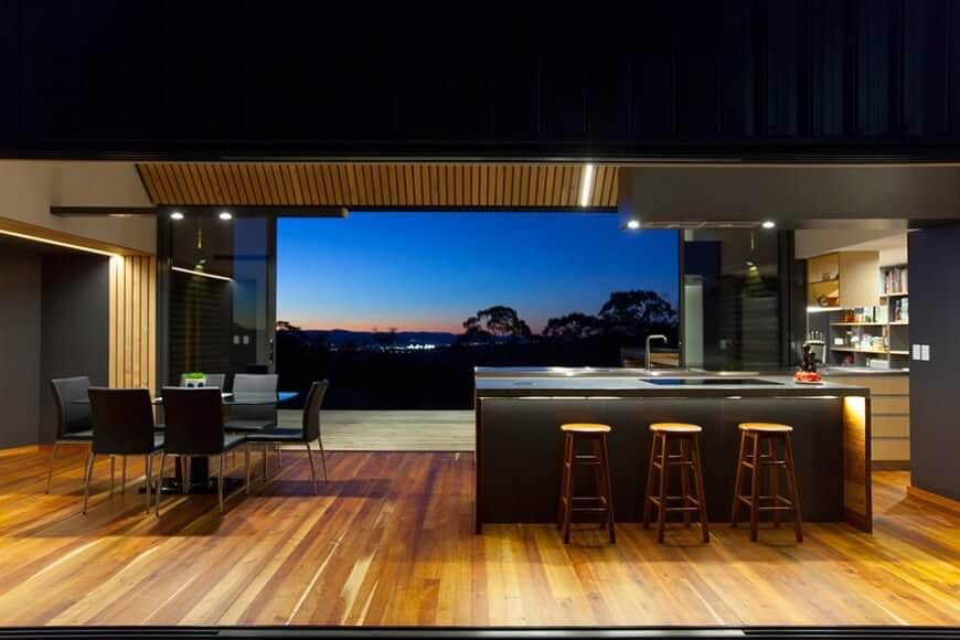 Contemporary open concept kitchen with black island, dining table and chairs and walls offset with plenty of natural wood.