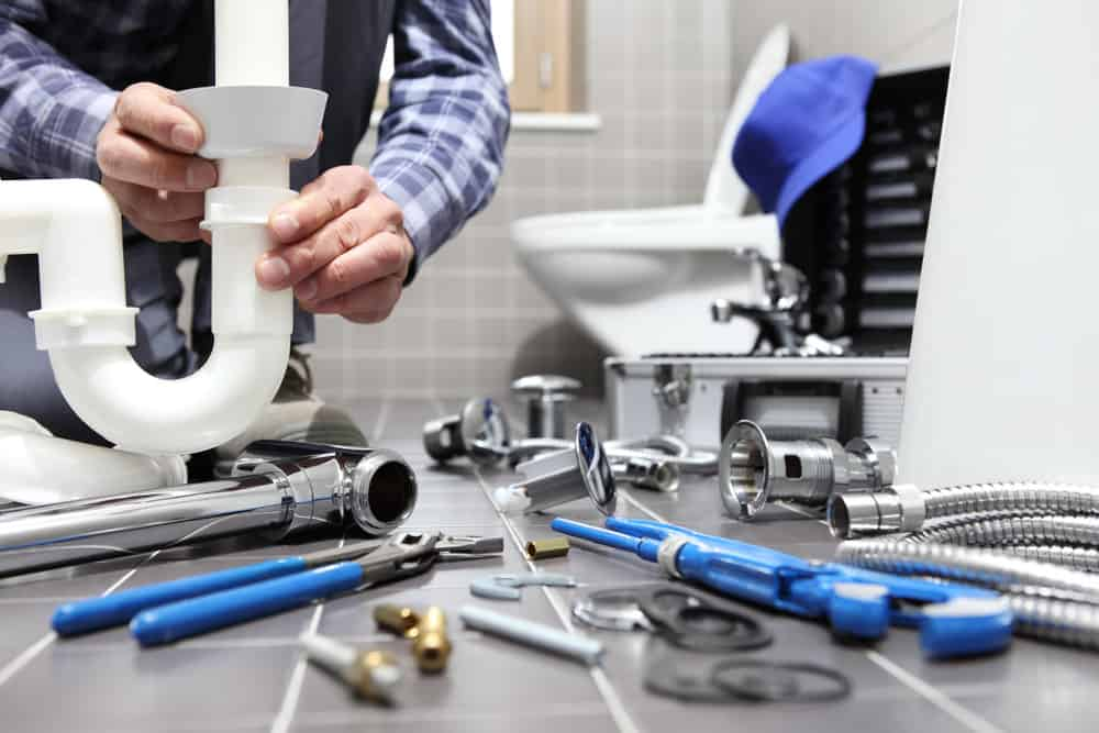 Plumber working on fixing toilet in bathroom