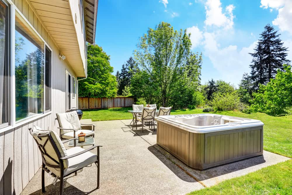 Portable hot tub on patio in backyard
