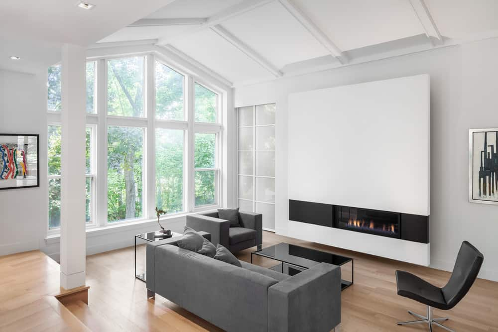 Modern home featuring a small formal living area featuring a stylish gray sofa set in front of the cozy fireplace.
