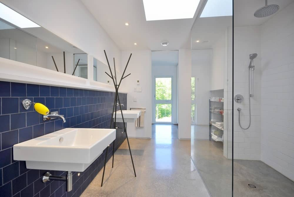 This primary bathroom has a white brick walk-in shower and a pair of floating washstands mounted on a blue tiled wall.