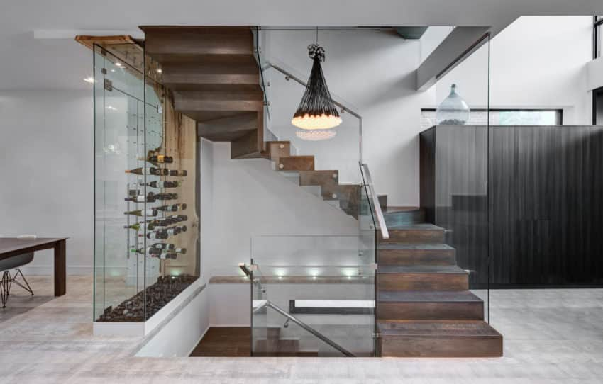 Fabulous 3/4 turn wooden staircase with glass balustrade and glass wine case on one side.