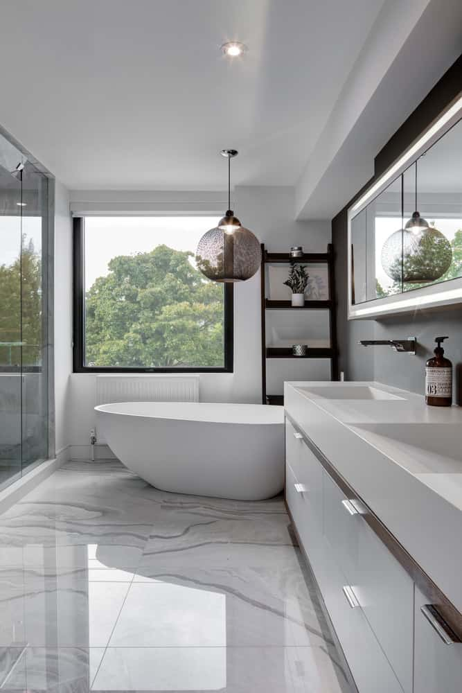 Master bathroom with tray-like sinks in modern white vanity next to a white free standing tub and opposite the glass walk in shower.