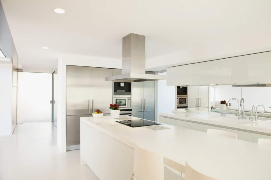 Here's a stark white contemporary kitchen design with super long island and a minimalist vibe.