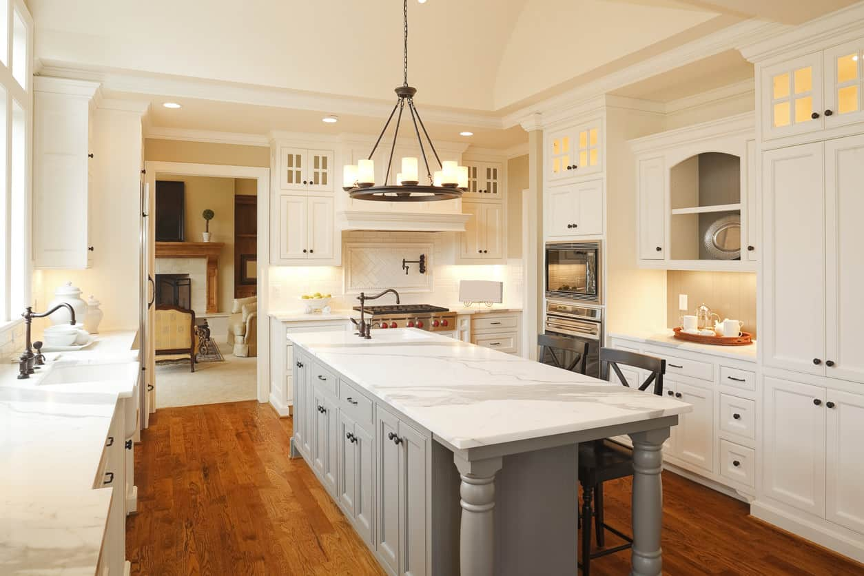 Who doesn't love a nicely done white farmhouse style kitchen? I love the wooden chandelier above the island. Check out the curved bronze faucets which gives it a farmhouse vibe. It's easy to miss, but the ceiling curves upward into a barrel ceiling design.