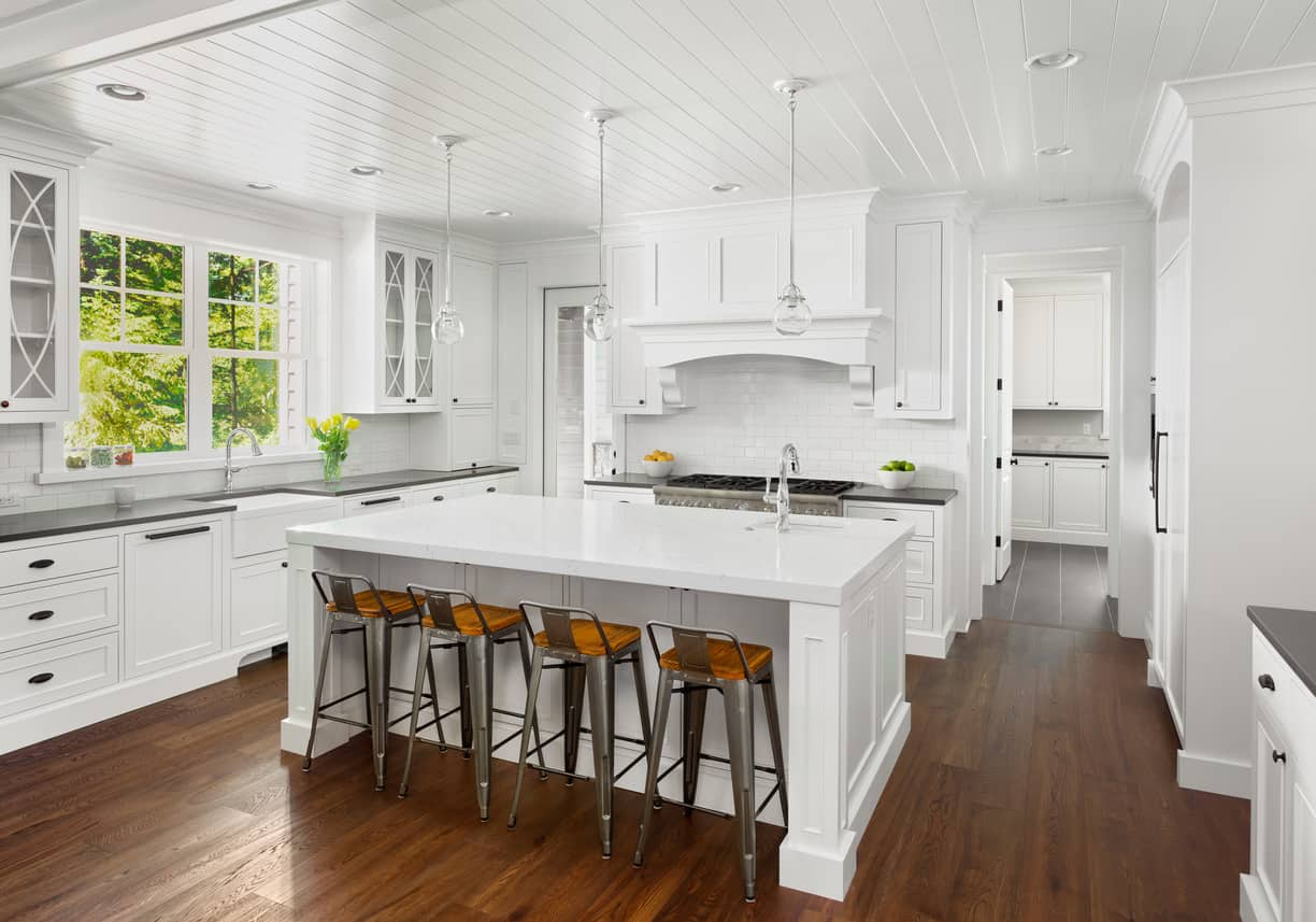 This pearl of a kitchen design is fabulous with stark white board ceiling with white base pendants on top of white range hood, backsplash, island... so much white except for that gorgeous wood floor and wood-seated stools.