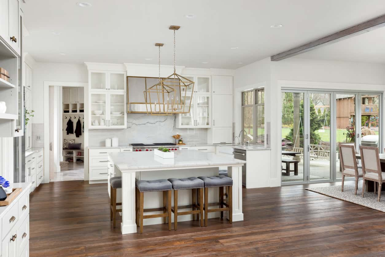 Large open concept white kitchen that has a huge square island (also white).