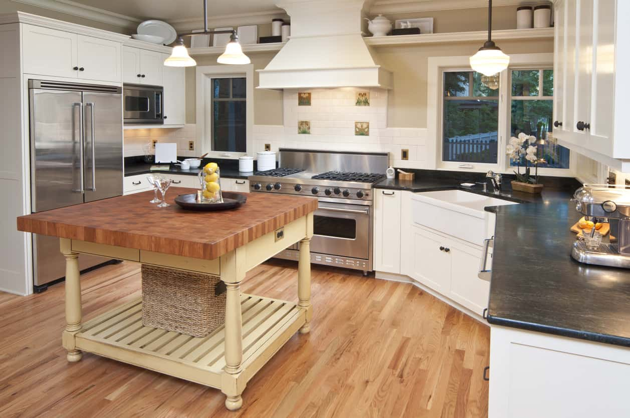 White kitchen with incredible butcher block island.