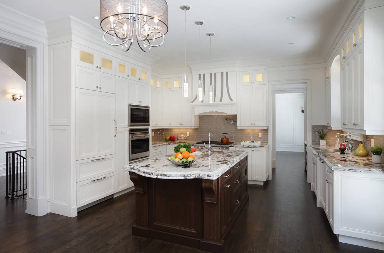 Luxurious white kitchen with large dark wood island and dark wood flooring. Includes white paneled refrigerator.