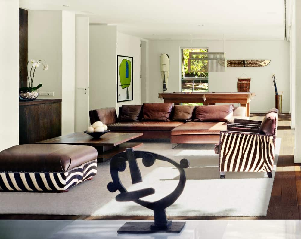 Large living room with a classy brown leather sofa with matching brown pillows set on a white rug. The chairs feature zebra pattern shades, adding style to the room's furniture.