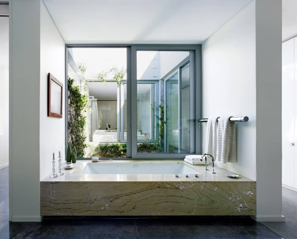 A large, square shaped bathtub with wide rims fits cozily in this neutral colored bathroom. The large windows looking out into a small garden and further down to another room give the space a sense of openness and calm. This is a great way to bring the outside natural beauty into the bathroom, which is rarely seen these days.