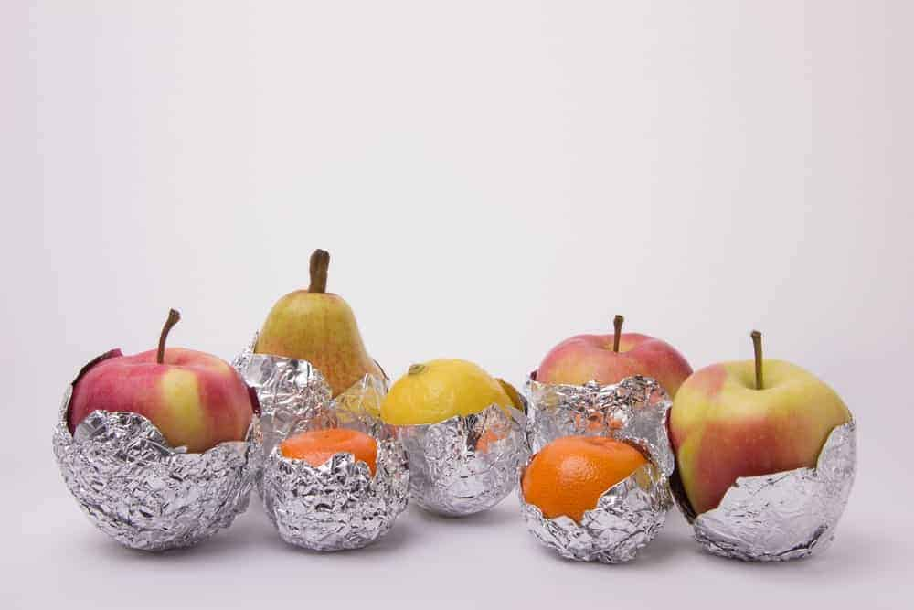 Apples, oranges, a pear, and a lemon individually half-wrapped in aluminum foil.