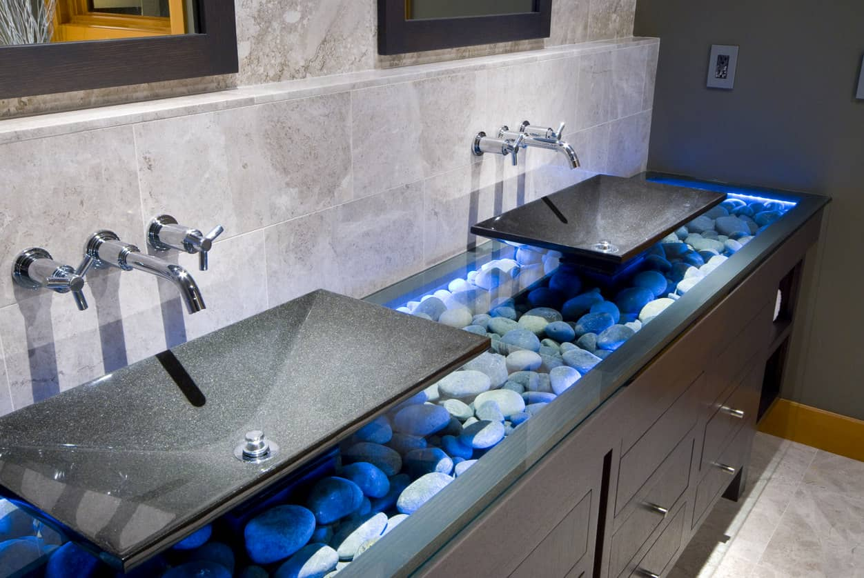 If there was ever a unique design for sinks, it's this! A bed of rocks rimmed with blue LED lighting gives a futuristic touch to a classic dark wood cupboard beneath. The black sinks with mounted faucet and taps finish the look.