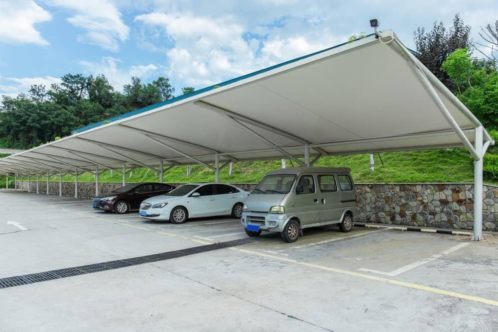 Vehicles parked under a steel awning.