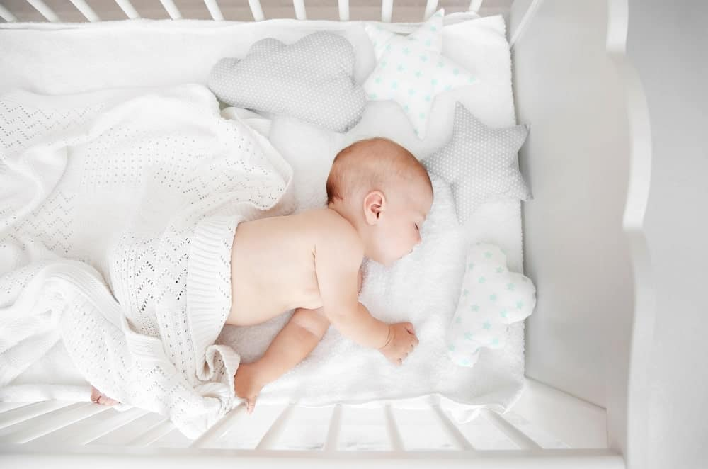 Top view of a baby sleeping peacefully on the crib.