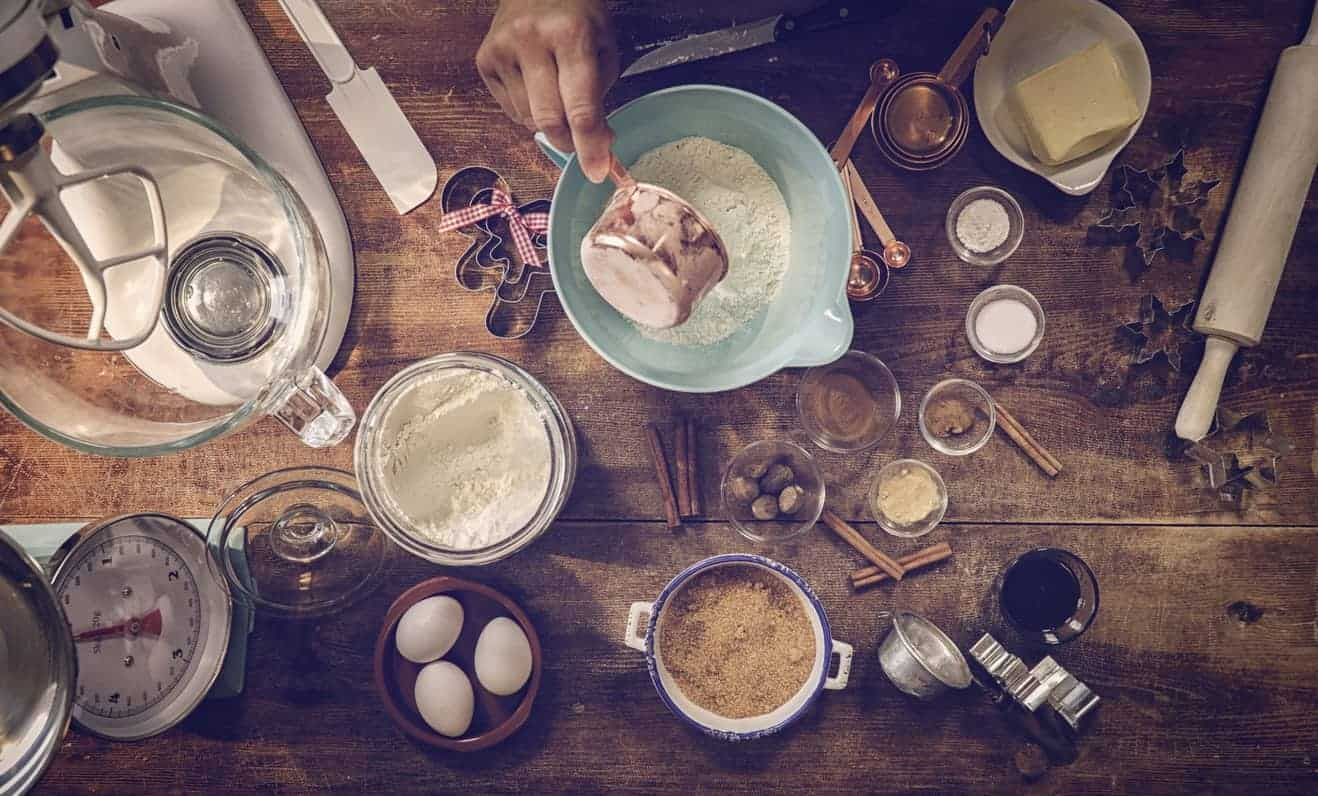Top view of baking tools and ingredients on wooden table.