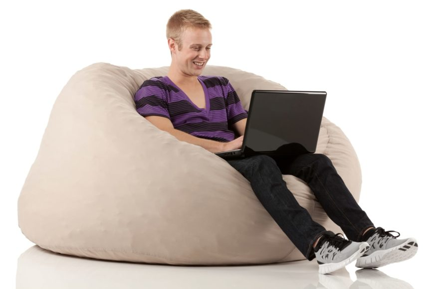 A young man works on his laptop while sitting on a beanbag chair.