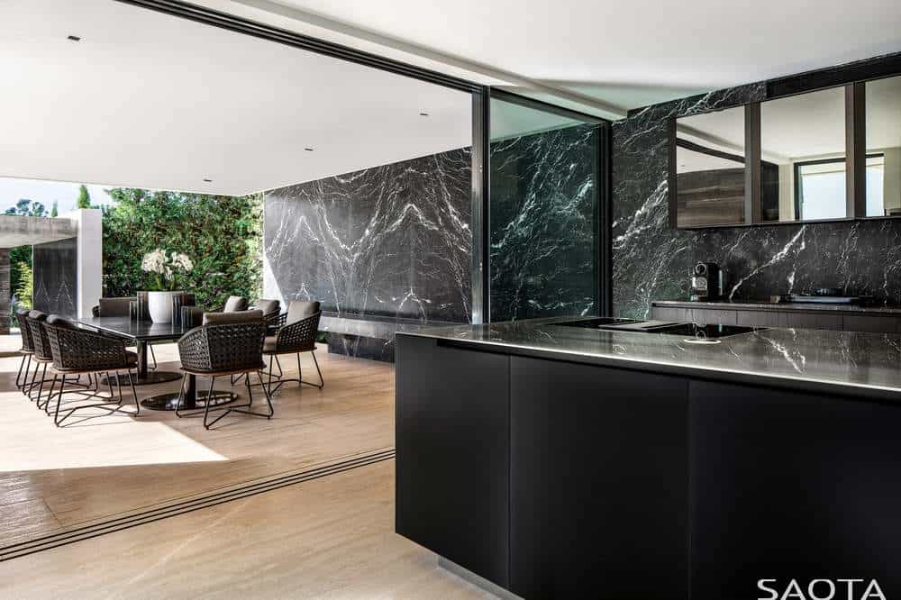 This sleek and modern kitchen has a pitch black kitchen island that matches with the peninsula. These are both complemented by the black marble design of the wallpaper that contrasts the white ceiling and light hardwood flooring.