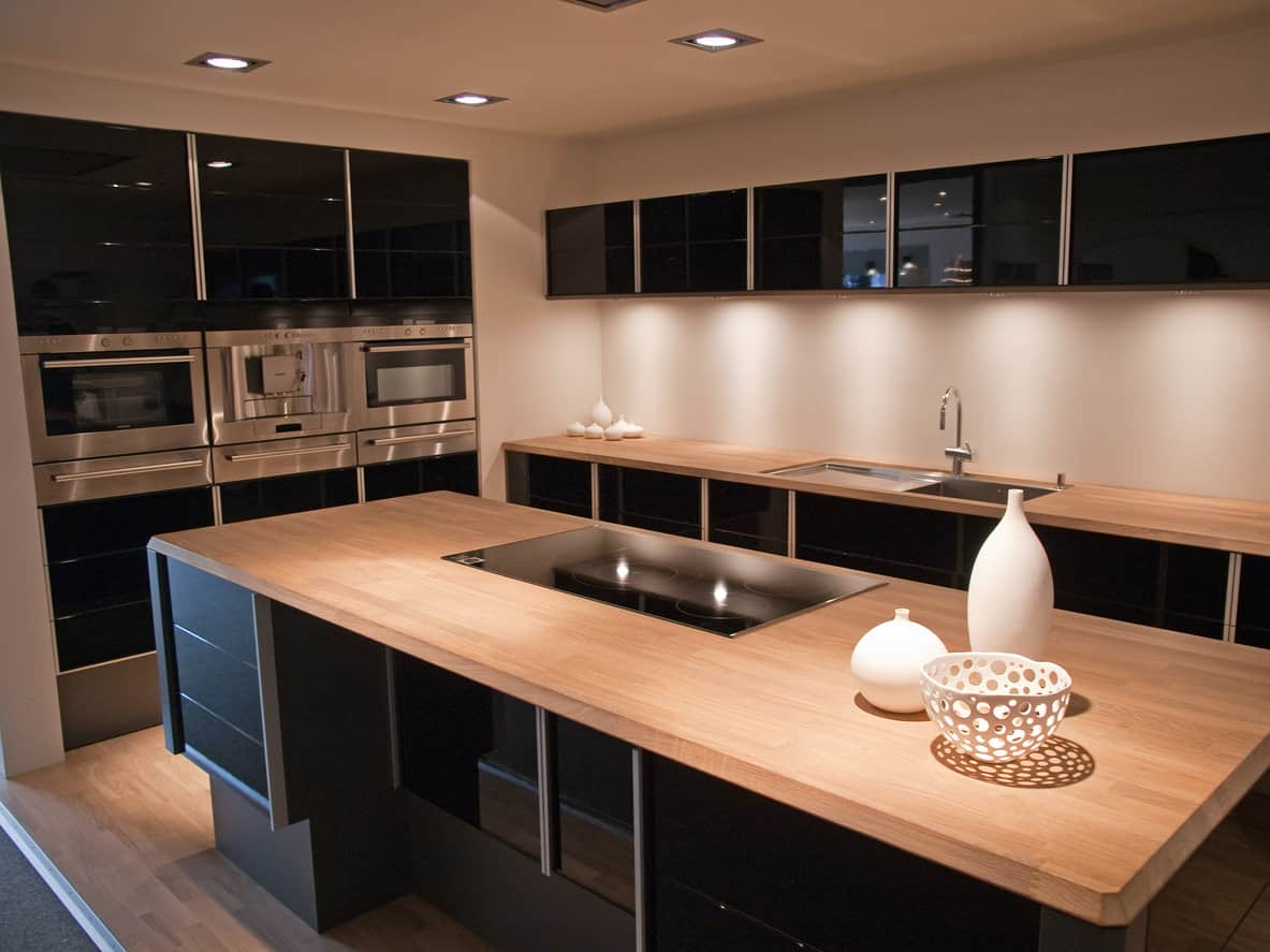 Black kitchen cabinets are tempered here with the light wood island and countertops. It's a fantastic color scheme that creates a beautiful and dramatic kitchen. The floor matches the countertops.