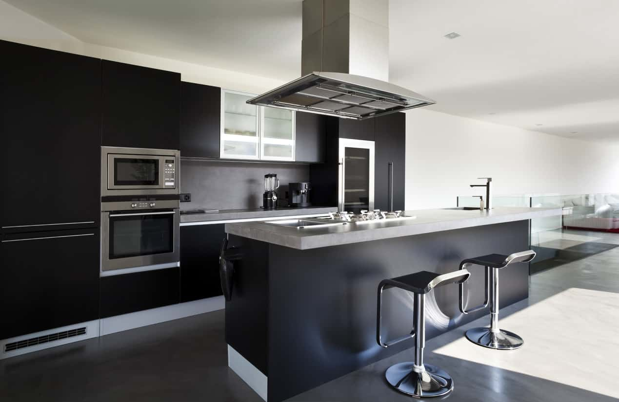 Modern single line kitchen with black modern cabinets and island contrasted nicely with light gray countertops and chrome bar stools.