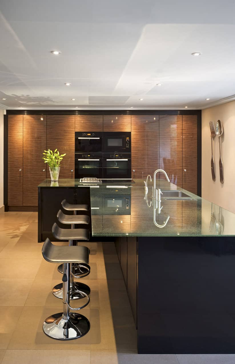 This somewhat black kitchen has a large black island, black upholstered stools only.
