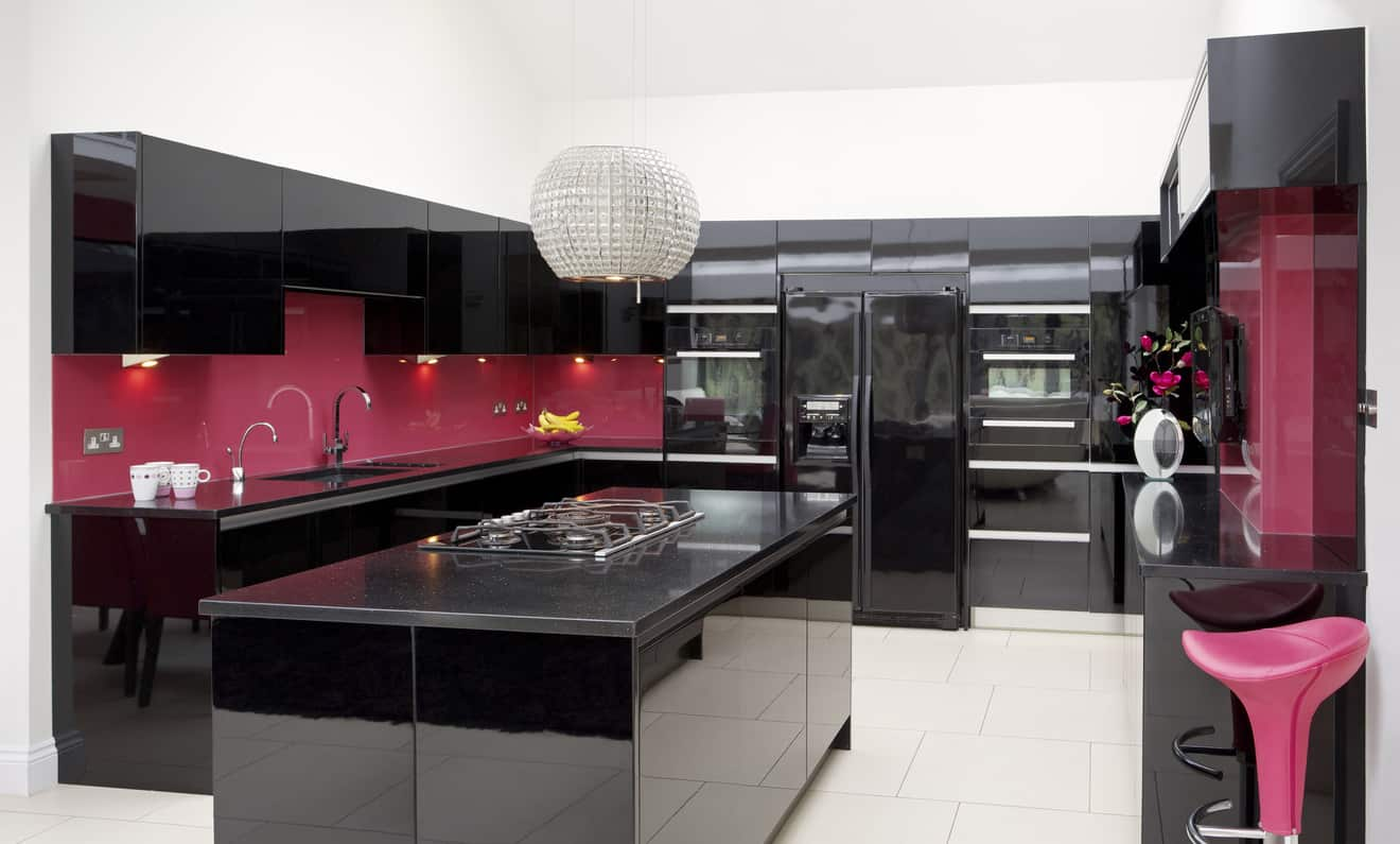 Spacious modern u-shaped black and pink kitchen. Notice the extensive glossy black kitchen cabinets, black island and black countertops contrasted with bright pink backsplash.
