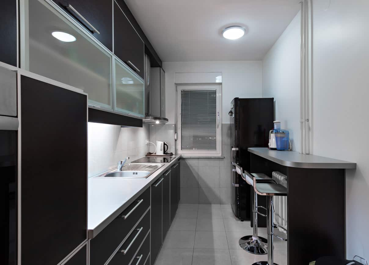 Small black apartment kitchen with stainless steel edging and hardware. Gray tile floor reduces stark contrast a white floor would creat. The glass-faced upper cabinets make the design less severe.