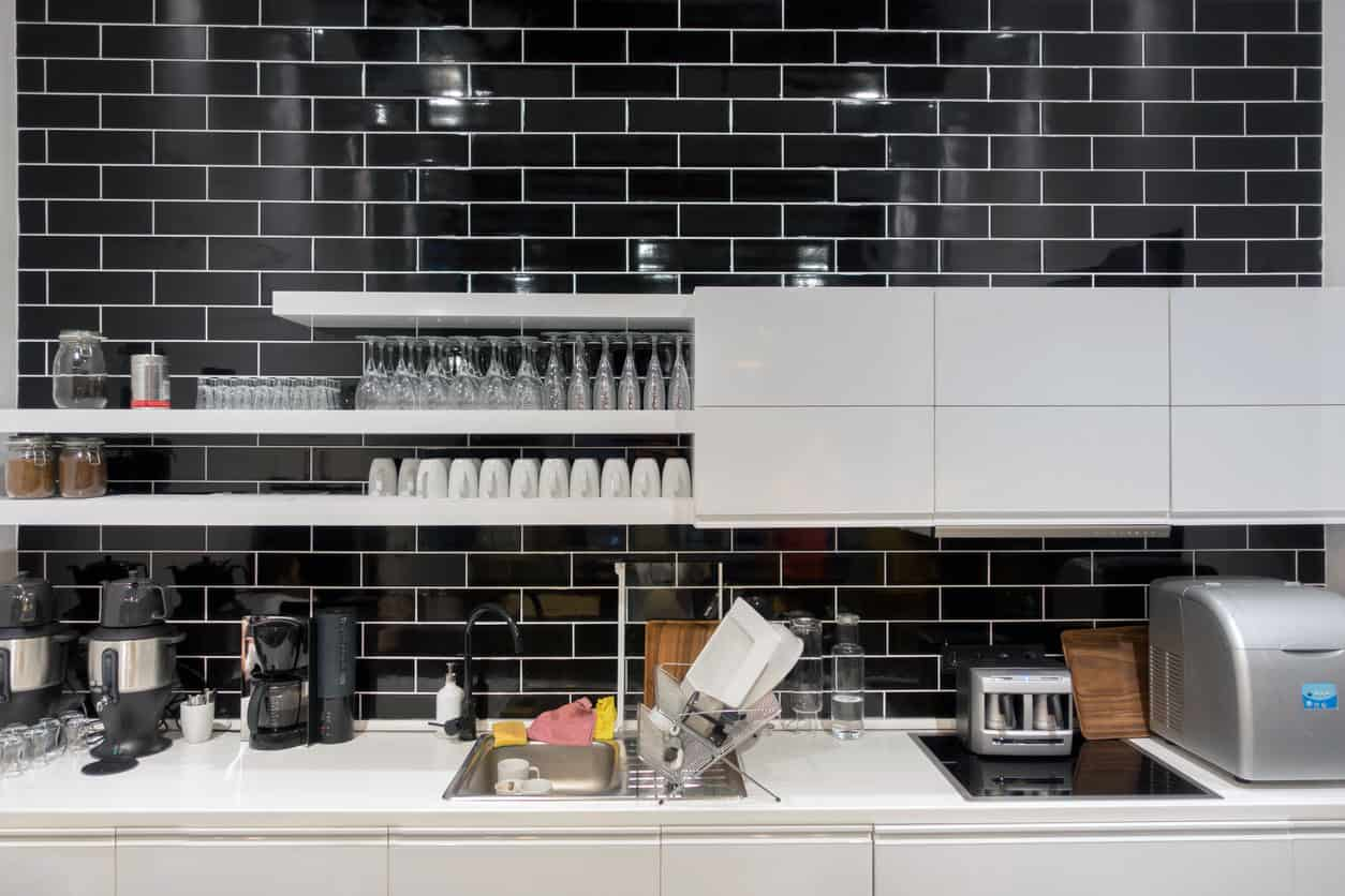 Here's a close-up image of a kitchen with black subway tile backsplash contrasting with white cabinets and countertops.