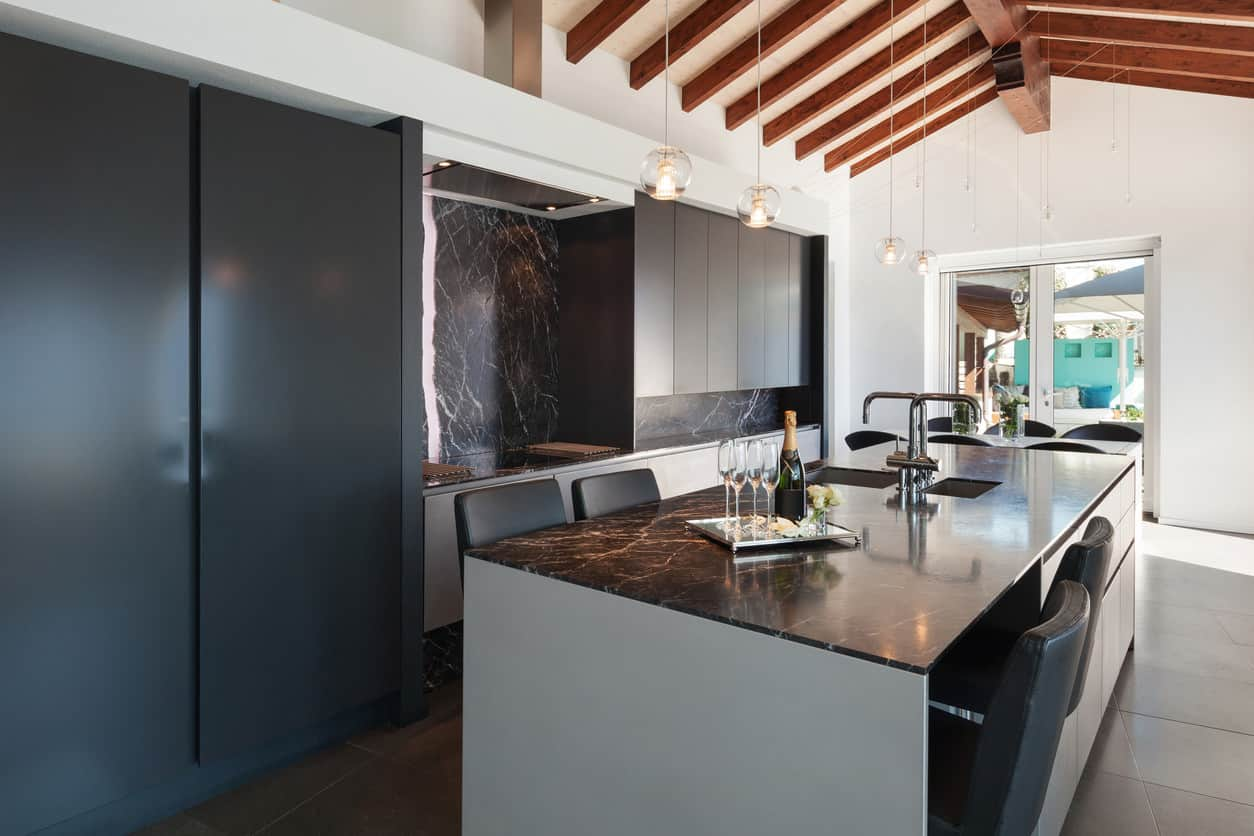 Kitchen with black cabinetry, black backsplash and black island surface. It's in a kitchen space with <a class=