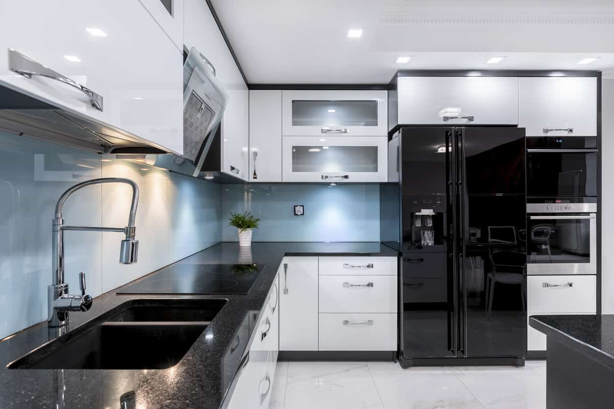 Fabulous white and black kitchen. White cabinets contrasted with black countertops and black appliances and then all tied together with a metallic blue backsplash.