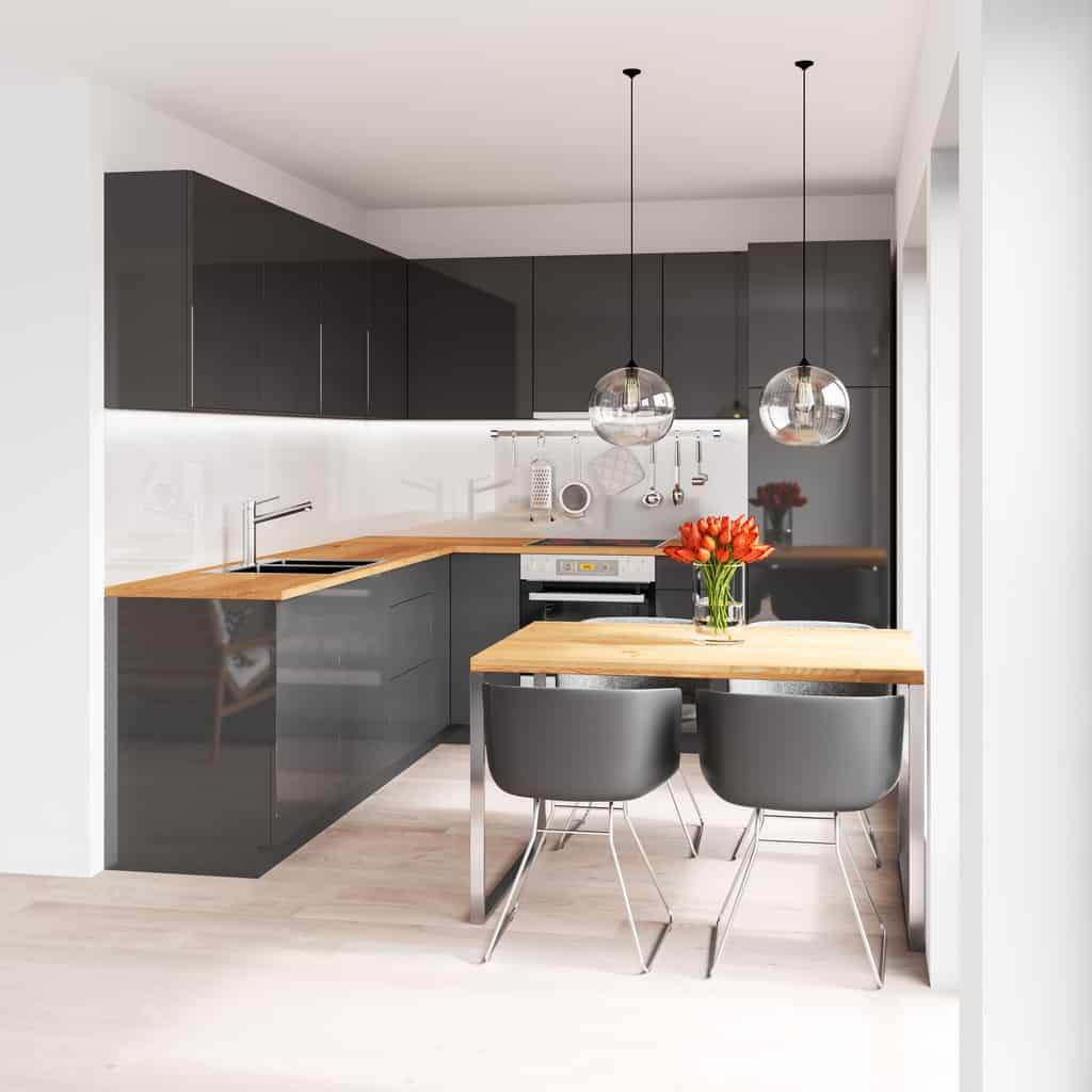 Small L-shaped black kitchen cabinets with wood countertop. The small kitchen dining table has a wood surface that matches the countertops. The chairs match the cabinets. This is a very handsome small kitchen design.