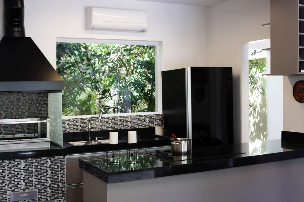 Close-up photo of a kitchen with black countertops, black and gray backsplash and black refrigerator.