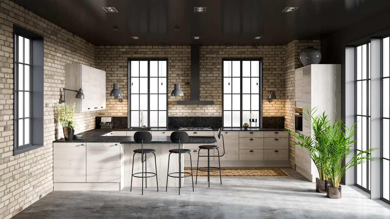 Industrial loft kitchen with black countertops, black cabinet hardware, black range hood and black ceiling. This is an example of a kitchen incorporating black without looking too dark due to the ligth brick walls, white cabinets and windows.