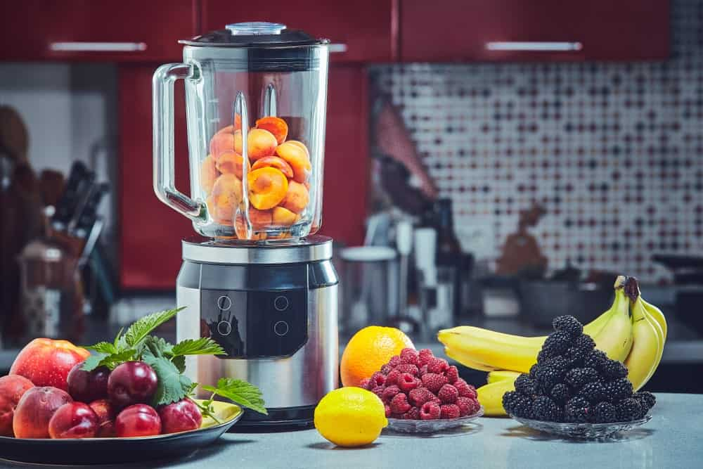 A blender filled with fruits stands on a kitchen counter surrounded by different types of fruits.