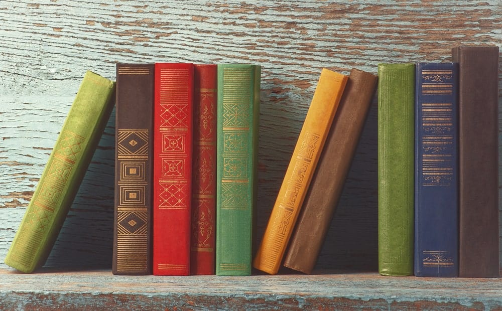 Old books on old wooden shelf.