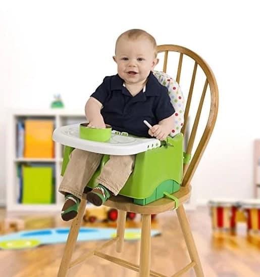 Yemek için yükseltici koltukta oturan bebek.