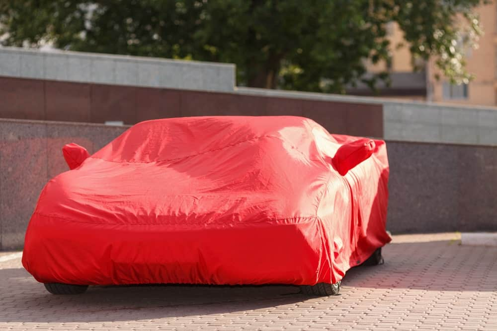 A sports car parked outdoors and protected by a red car cover.
