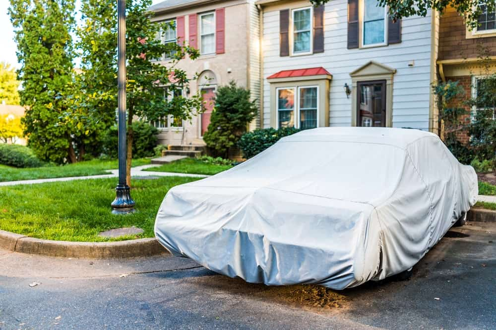 Car parked outside the house protected with car cover.