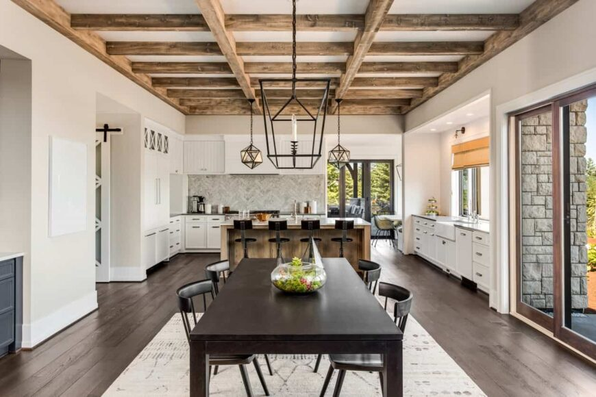 Farmhouse style open space interior with beam ceiling and Industrial lights over the dining table and breakfast island.