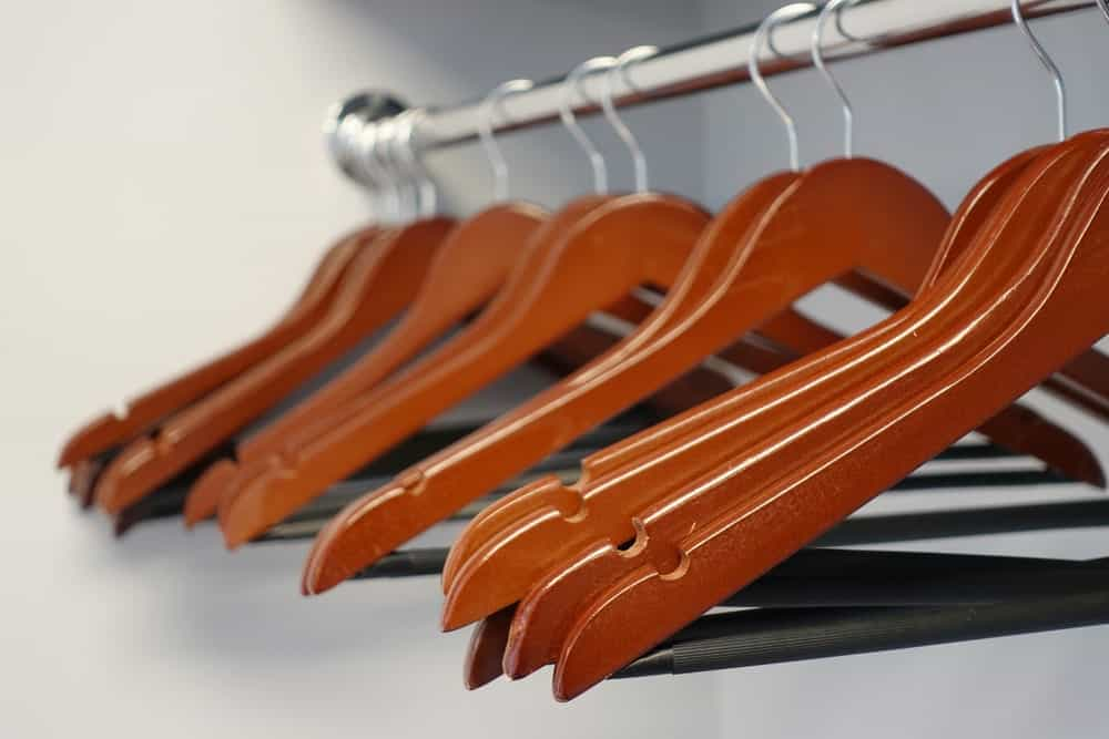 Wood coat hangers on a curtain rod.